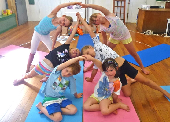 This is an image of children in a kids yoga class creating the sydney opera house with yoga poses.