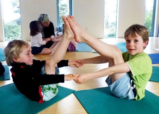 This is an image of two boys doing a yoga partner pose to make a boat.