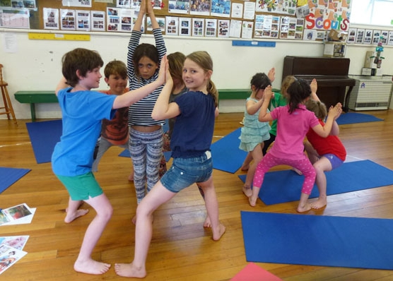 This is an image of children creating group temples in japan with yoga poses.
