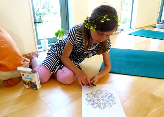 This is a girl in outward meditation colouring a mandala in a kids yoga class.