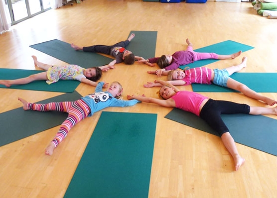 This is an image of children lying on the floor doing a yoga group pose as a snowflake.