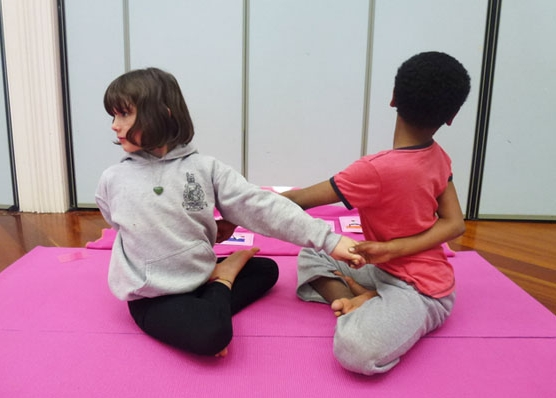 This is an image of two children doing a yoga pretzel twisting partner pose.