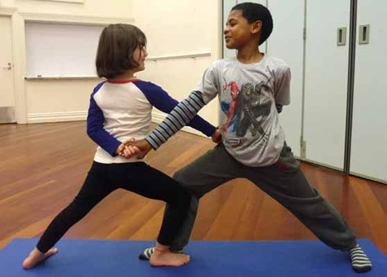 This is an image of two children doing a partner yoga pose as warrior friends.