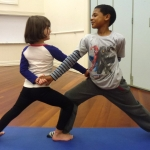 This is an image of two children doing a peaceful warrior partner yoga pose.
