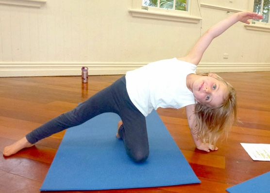 This is an image of a girl doing a side-stretching yoga pose called gate pose.