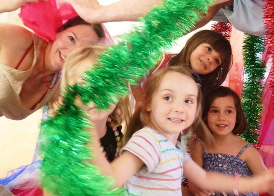 This is an image of children in a kids yoga class helping santa's elves wrap yoga presents,