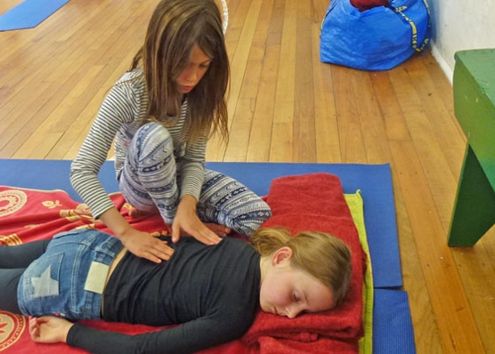 This is an image of two children giving each other a massage in a kids yoga class.