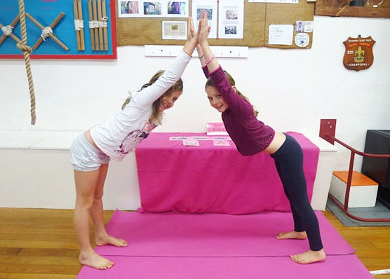 This is an image of two kids doing a yoga house partner pose.