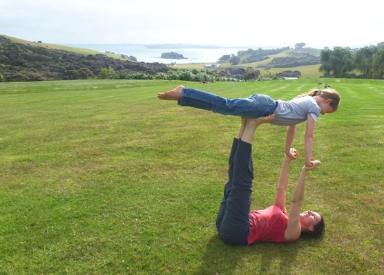 This is an image of mother and child doing acroyoga flying pose on Waiheke Island.