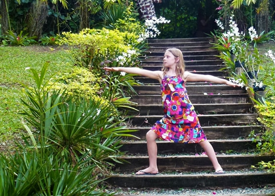 This is an image of a beautiful young girl doing a warrior two yoga pose in Fiji.