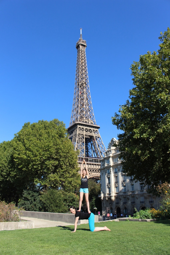 This is a photo of Michaela and Isla from Yogi Kids doing an Eiffel Tower yoga pose in Paris