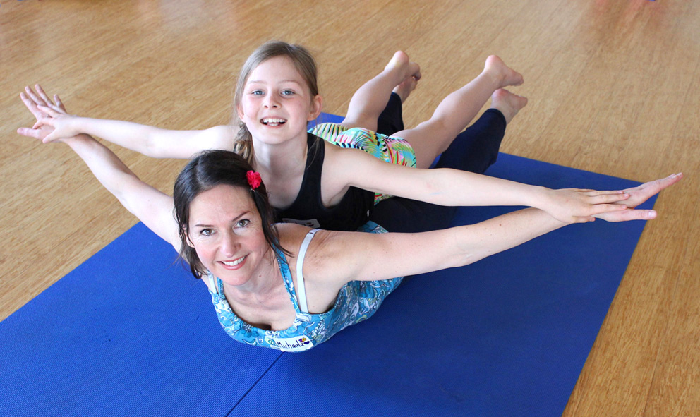 This is a photo of Michaela director of Yogi Kids and her daughter doing a manta ray yoga pose.